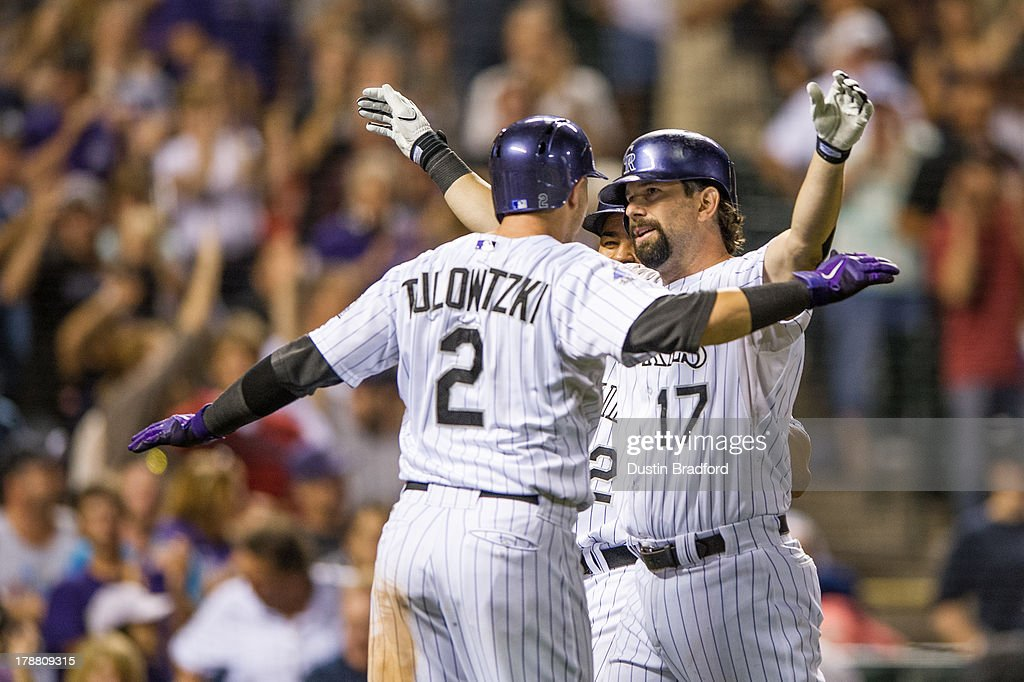 <a gi-track='captionPersonalityLinkClicked' href=/galleries/search?phrase=Todd+Helton&family=editorial&specificpeople=200735 ng-click='$event.stopPropagation()'>Todd Helton</a> #17 of the Colorado Rockies celebrates his second three-run home run of the game for his 2,499th career hit with <a gi-track='captionPersonalityLinkClicked' href=/galleries/search?phrase=Troy+Tulowitzki&family=editorial&specificpeople=757353 ng-click='$event.stopPropagation()'>Troy Tulowitzki</a> #2 in the seventh inning of a game against the Cincinnati Reds at Coors Field on August 30, 2013 in Denver, Colorado. The Rockies beat the Reds 9-6.
