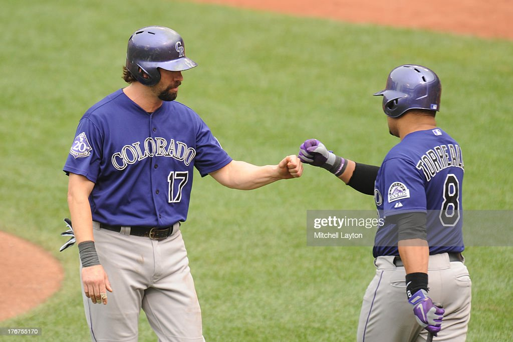 <a gi-track='captionPersonalityLinkClicked' href=/galleries/search?phrase=Todd+Helton&family=editorial&specificpeople=200735 ng-click='$event.stopPropagation()'>Todd Helton</a> #17 of the Colorado Rockies celebrates scoring the team's first run with Yorvit Torrealba #8 on a Charlie Blackman #19 double in the seventh inning against the Baltimore Orioles on August 18, 2013 at Oriole Park at Camden Yards in Baltimore, Maryland. The Orioles won 7-2.
