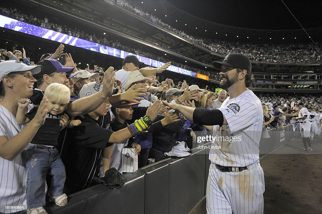 Todd Helton (17) of the Colorado Rockies high fives the crowd as he enters the dugout after walking off the field at the end of the game against the Boston Red Sox September 25, 2013 at Coors Field. Helton will retire at the end of the season after 17 years with the club.