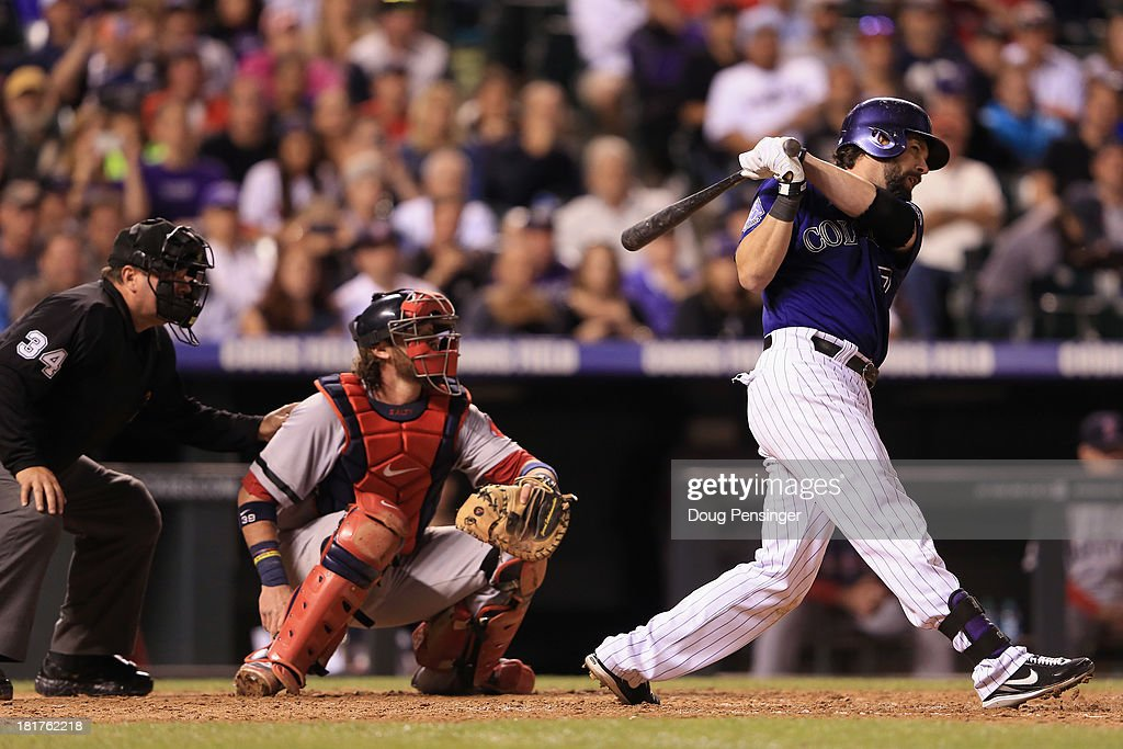 Todd Helton #17 of the Colorado Rockies hits a single as catcher Jarrod Saltalamacchia #39 of the Boston Red Sox backs up the plate and umpire Sam Holbrook oversees the action at Coors Field on September 24, 2013 in Denver, Colorado.