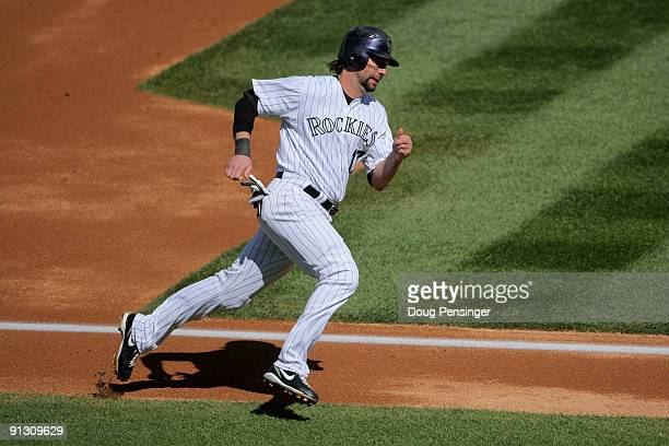 Todd Helton of the Colorado Rockies rounds third to score on an RBI single by Garrett Atkins off of starting pitcher Manny Parra of the Milwaukee...