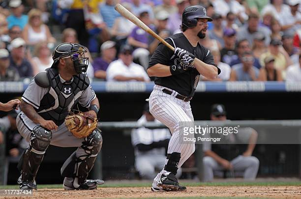 Todd Helton of the Colorado Rockies singles in the third inning as catcher Ramon Castro of the Chicago White Sox backs up the plate during...