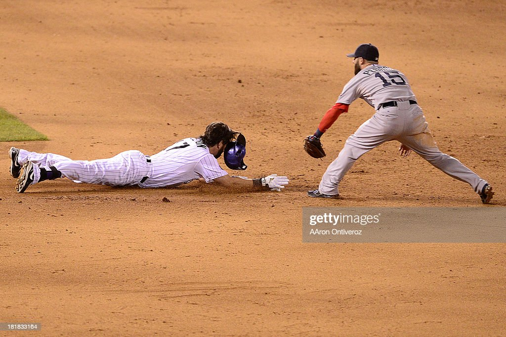 Todd Helton (17) of the Colorado Rockies slides beneath a tag by Dustin Pedroia (15) of the Boston Red Sox upon hitting a double during the action in Denver. The Colorado Rockies hosted the Boston Red Sox and said farewell to longtime first baseman Todd Helton, who recently announced his retirement following this season.