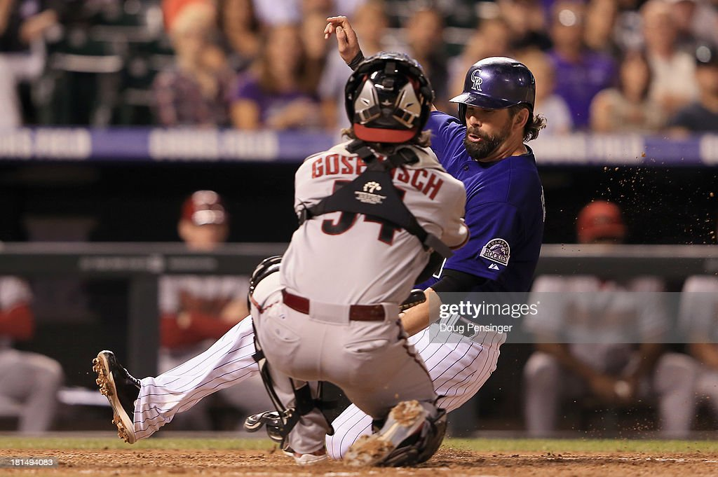 <a gi-track='captionPersonalityLinkClicked' href=/galleries/search?phrase=Todd+Helton&family=editorial&specificpeople=200735 ng-click='$event.stopPropagation()'>Todd Helton</a> #17 of the Colorado Rockies slides home past catcher Tuffy Gosewisch #54 of the Arizona Diamondbacks to score on a sacrifice fly by Jordan Pacheco #15 of the Colorado Rockies as the Diamondbacks held a 6-1 lead in the fourth inning at Coors Field on September 21, 2013 in Denver, Colorado.