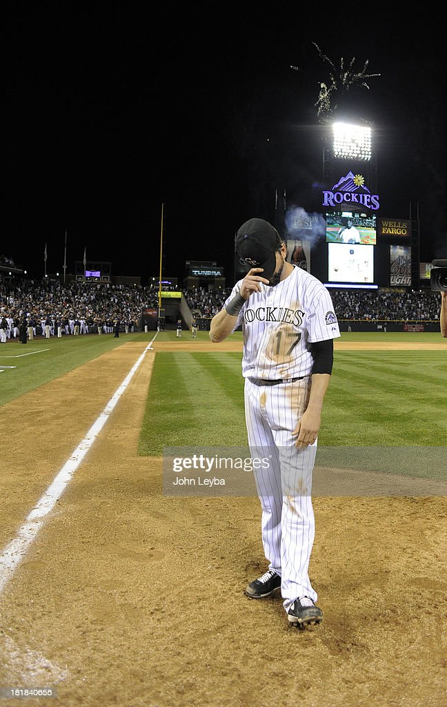 Todd Helton (17) of the Colorado Rockies slowly [puts hit aht back on after waving to the crowd after taking a lap around the field at the end of the game against the Boston Red Sox September 25, 2013 at Coors Field. Helton will retire at the end of the season after 17 years with the club.