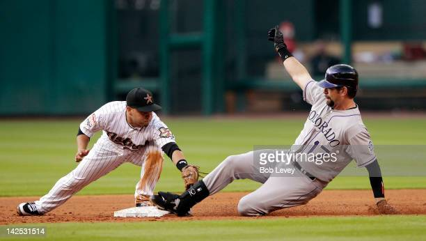 Todd Helton of the Colorado Rockies stretches a single into a double as second baseman Jose Altuve of the Houston Astros is late on the tag during...