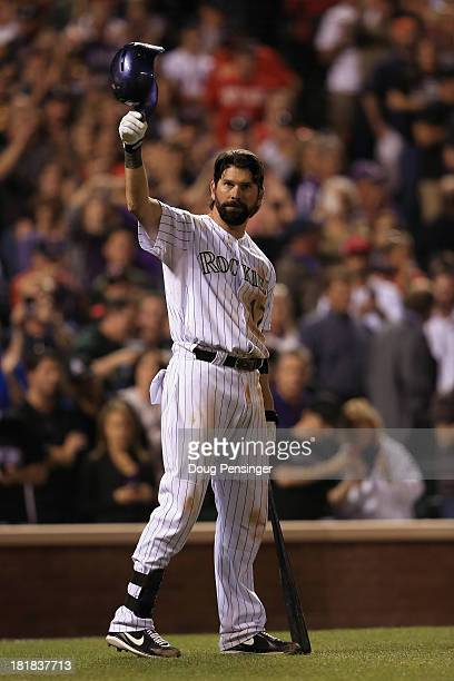 Todd Helton of the Colorado Rockies tips his hat to the standing ovation of fans as he prepares to take an at bat against the Boston Red Sox during...