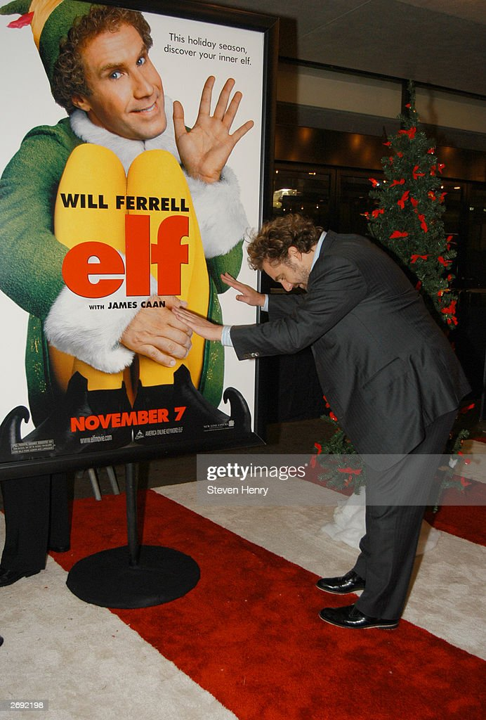 Todd Komarnicki producer of Elf bows before a poster of his movie at a special screening of Elf to benefit the TJ Martell Foundation at Loews Astor...