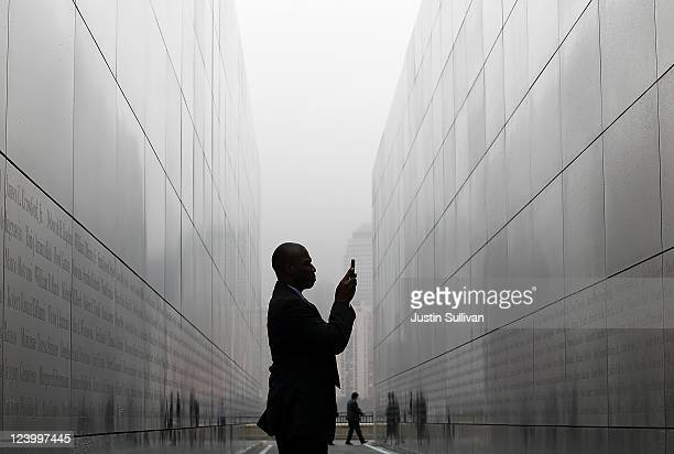 Todd McCormick takes a photograph with is cell phone of names on the walls of the newly constructed 'Empty Sky Memorial' at Liberty State Park on...