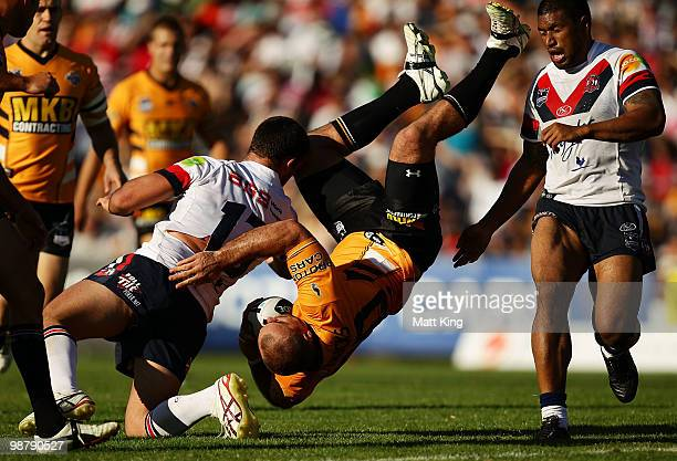 Todd Payton of the Tigers is tackled in a dangerous position by Nate Myles of the Roosters during the round eight NRL match between the Wests Tigers...