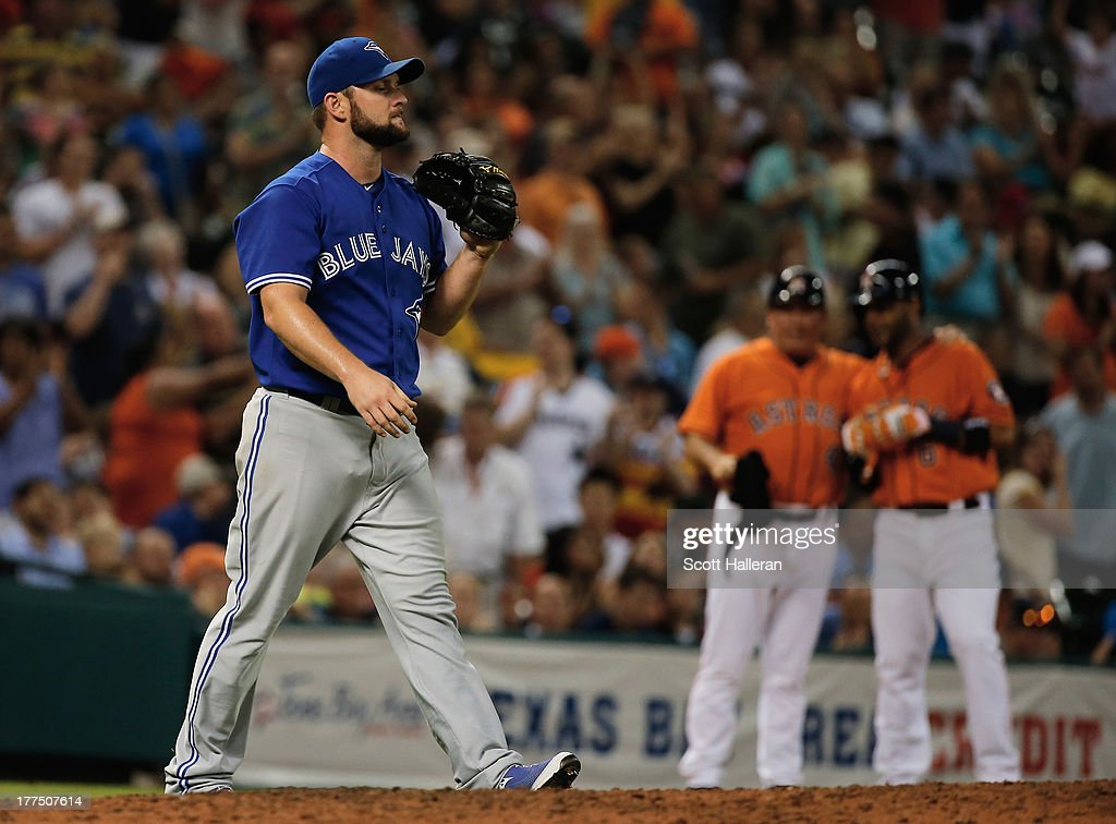 Todd Redmond #58 of the Toronto Blue Jays reacts to allowing a two run triple in the fourth inning against the Houston Astros at Minute Maid Park on August 23, 2013 in Houston, Texas.