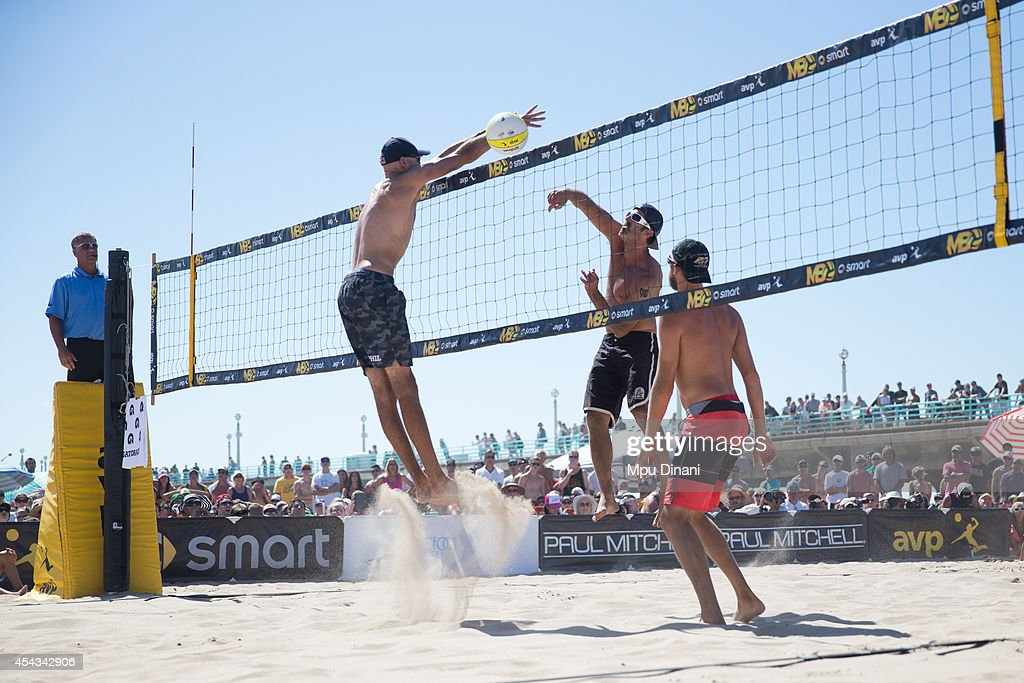 Todd Rogers spikes the ball against Phil Dalhausser as Theo Brunner looks on at the 55th AVP Manhattan Beach Open on August 17 2014 at Manhattan...