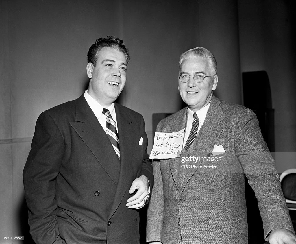 Todd Russell host of the CBS Radio quiz and game show, 'Strike It Rich' poses for a photo with contestant Ralph L. Bancroft of Browns Mills, N.J. Image dated: December 23, 1947 New York, NY.