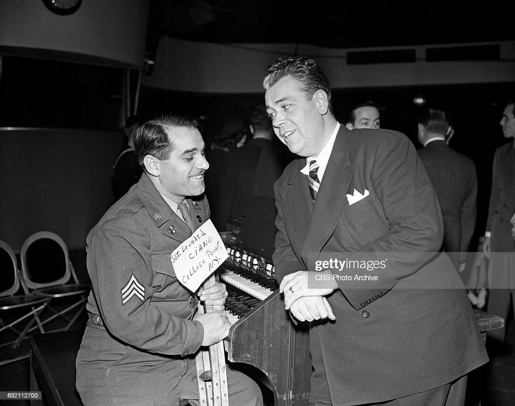 Todd Russell (pictured right) host of the CBS Radio quiz and game show, 'Strike It Rich' talks with SGT. Leonard Ciano from College Point, NY, who was a a contestant on the show. Image dated: December 23, 1947 New York, NY.