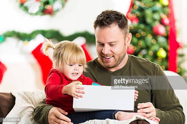 Todder girl opens gift at Christmas time
