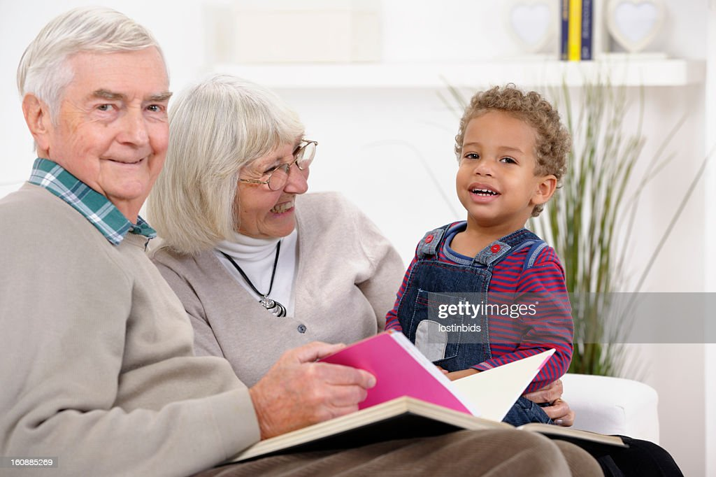 Toddler And Grandparents / Carers Enjoying Storytime : Stock Photo