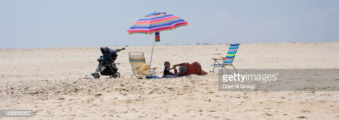 Toddler and his great-grandma on a beach blanket : Stock Photo
