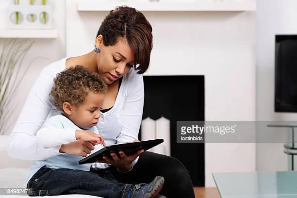 Bébé et jeune maman et sœur à l'aide d'une tablette numérique