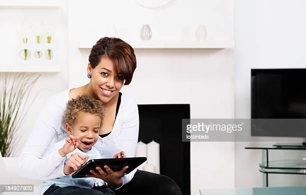 Bébé et jeune maman et sœur à l'aide de la tablette électronique