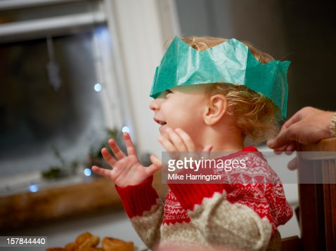 Toddler at Christmas dinner wearing paper hat. : Stock Photo