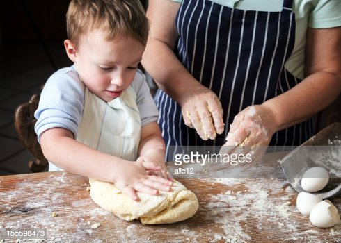 A toddler attempting to knead dough
