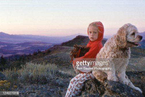 Toddler boy and her dog watch sunset : Stock Photo