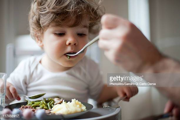 Toddler boy being fed green beans, cropped