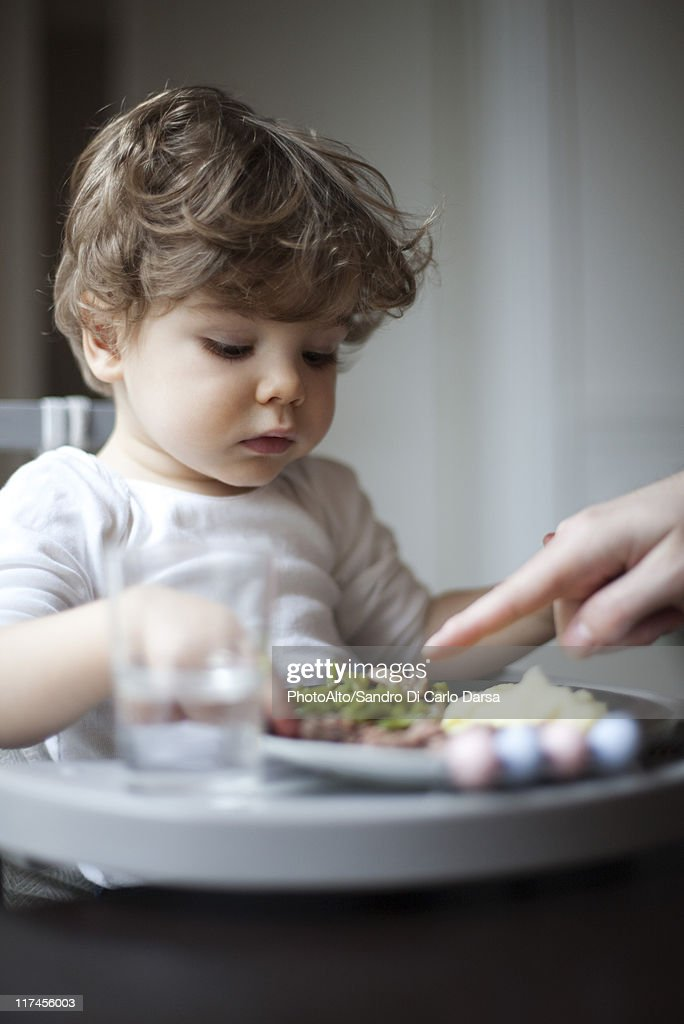Toddler boy being told to eat his vegetables, cropped : Stock Photo