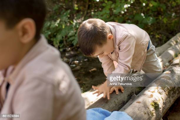 Toddler boy crawling on wooden posts