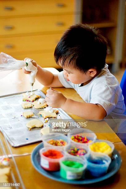 Toddler boy decorating sugar cookies