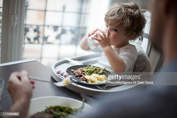 Toddler boy drinking glass of water