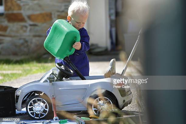 Toddler boy filling toy car with fuel from can