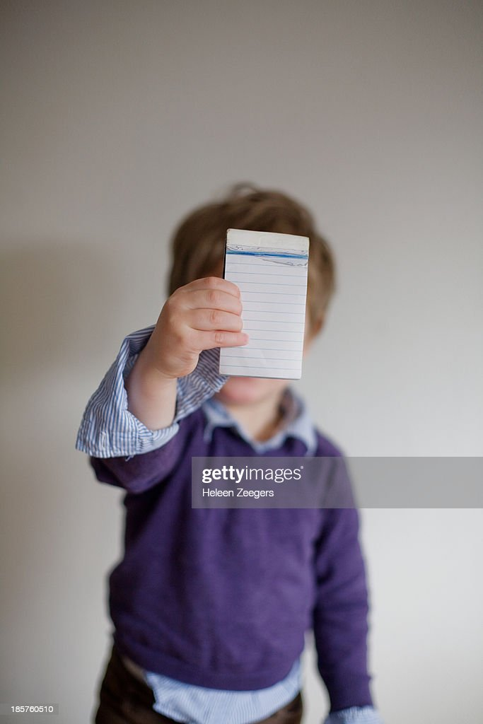 toddler boy holding blanc notepaper : Stock Photo