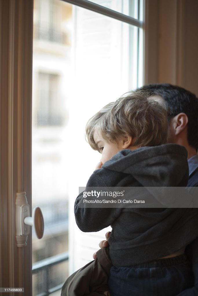 Toddler boy in father's arms, looking out window : Stock Photo