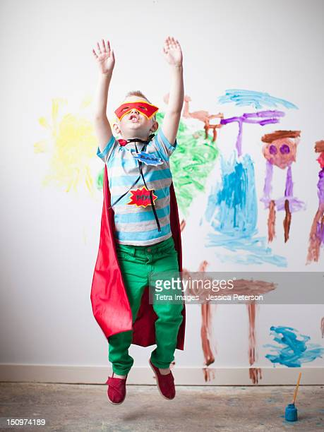 Toddler boy (2-3) in superhero costume jumping mid-air