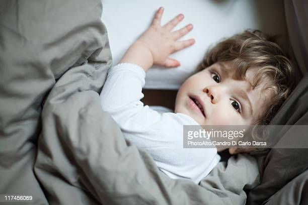 Toddler boy lying in bed, portrait