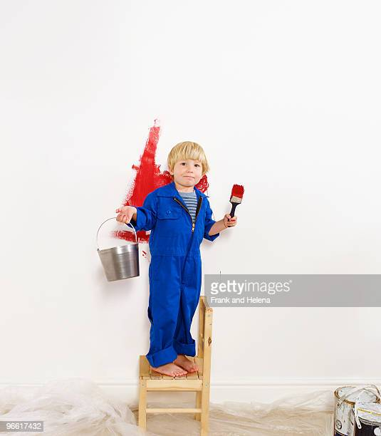 Toddler boy painting wall red.