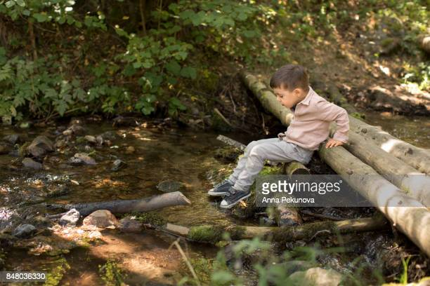 Toddler boy playing on a wooden bridge