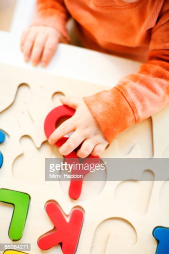 toddler boy playing with alphabet puzzle : Stock Photo