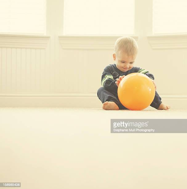 Toddler Boy Playing with Orange Ball