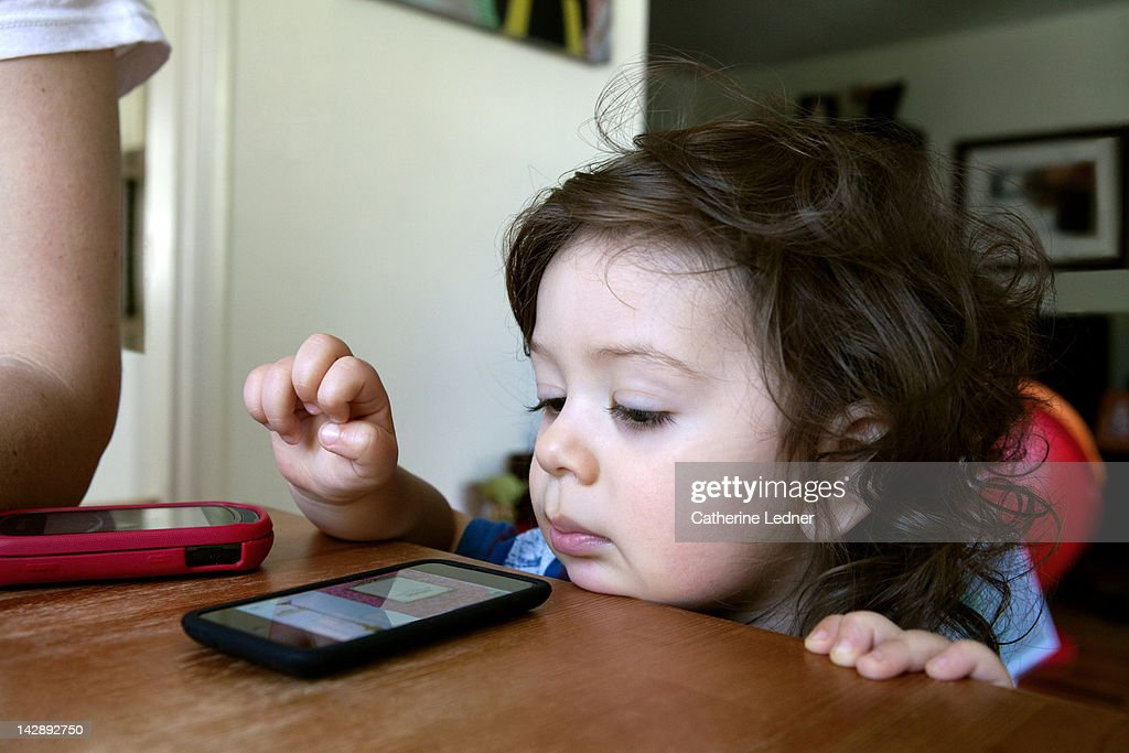 Toddler boy playing with smart phone. : Stock Photo