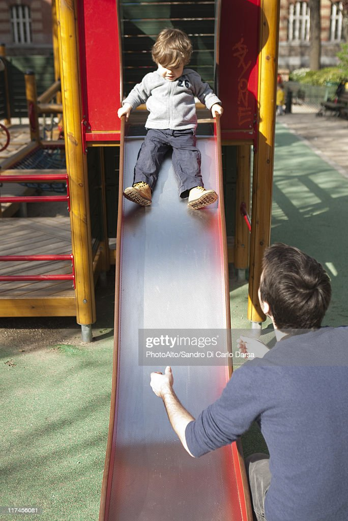 Toddler boy preparing to go down playground slide, father waiting at the bottom : Stock Photo