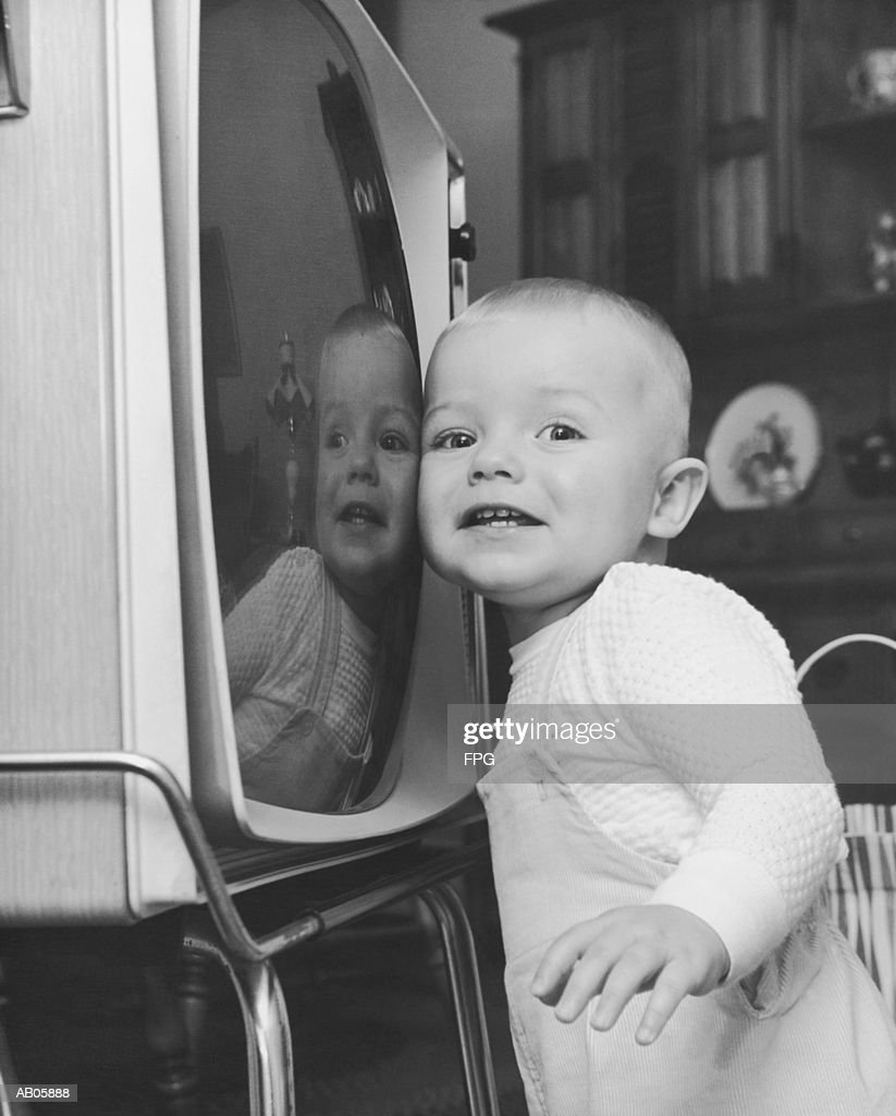 Toddler boy (18-21 months) pressing cheek against television (B&W) : Stock Photo