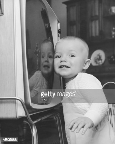 Toddler boy (18-21 months) pressing cheek against television (B&W) : Stock Photo