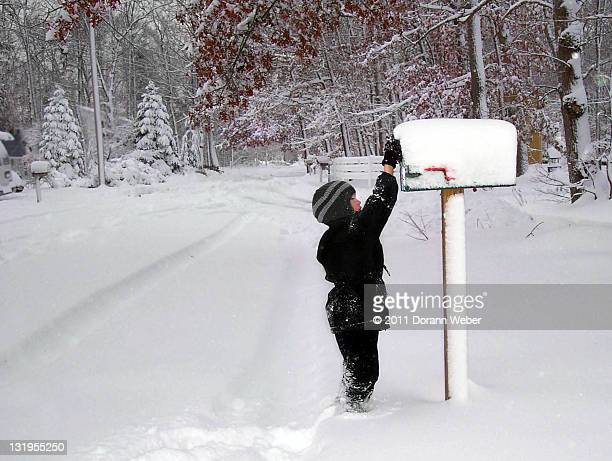 Toddler boy reaching for mail in snow