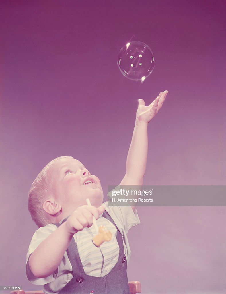 Toddler boy reaching to catch bubble. (Photo by H. Armstrong Roberts/Retrofile/Getty Images) : Stock Photo