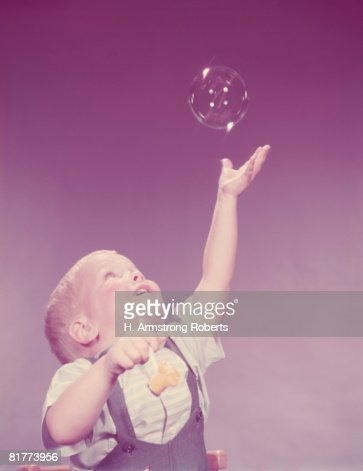 Toddler boy reaching to catch bubble. (Photo by H. Armstrong Roberts/Retrofile/Getty Images) : Foto de stock