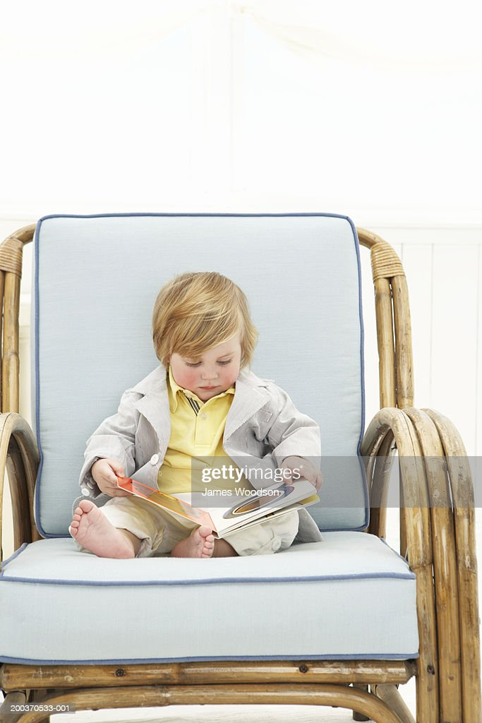 Toddler boy reading book in arm chair stock photo getty for Toddler reading chair