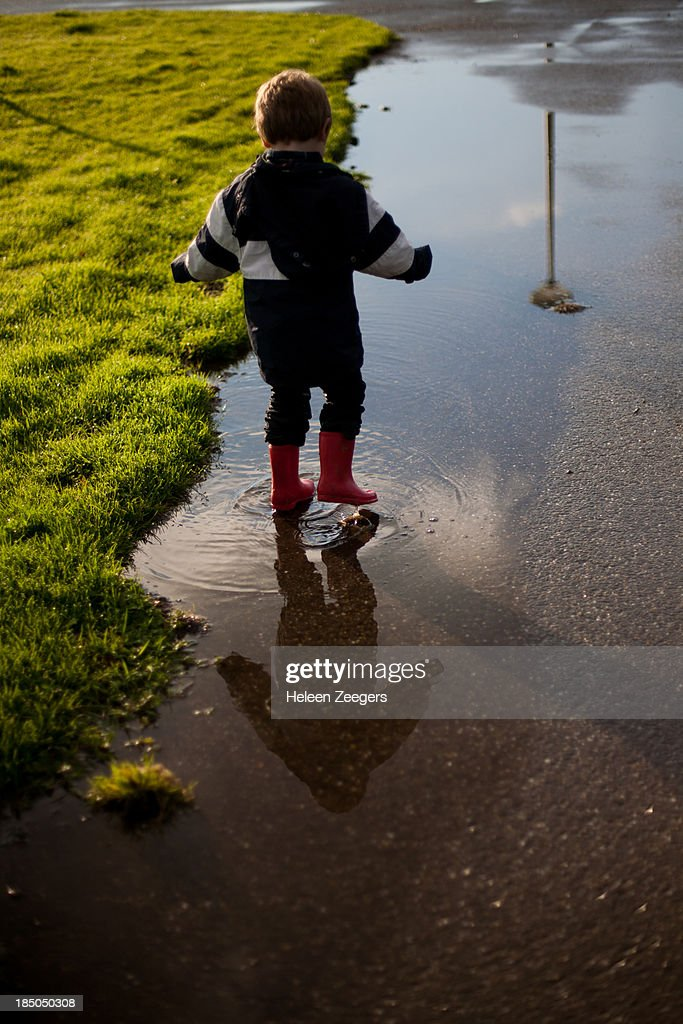 toddler boy reflection rain puddle red rainboots : Stock Photo