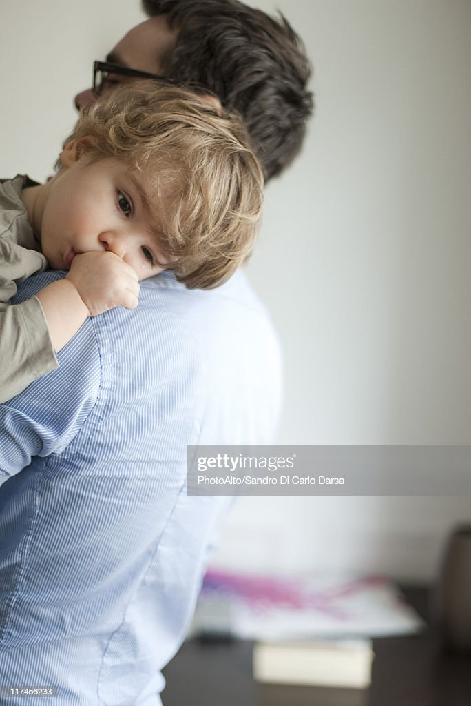 Toddler boy resting head on father's shoudler : Stock Photo
